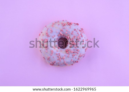Delicious bright juicy purple one sprinkled donut for a sweet tooth on a purple background. Close-up selective focus. Top view Delicious unhealthy baked goods with sugar.