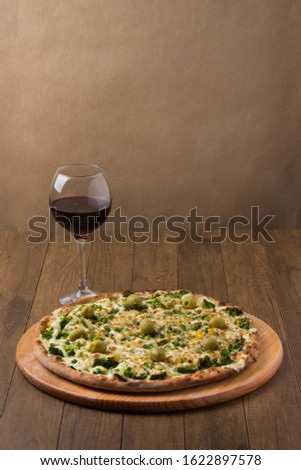 Delicious Broccoli Pizza served on wooden board. Baked with mozzarella, broccoli, corn, peas, olives and sauce. Olive oil, basil, glass of red wine. Centralized vertical photo. Refined food.