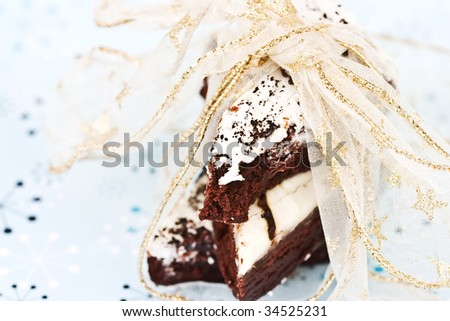 Delicious brownies tied with a Christmas ribbon on a blue holiday decorative background. Shallow DOF with focus on top brownie and ribbon. - stock photo
