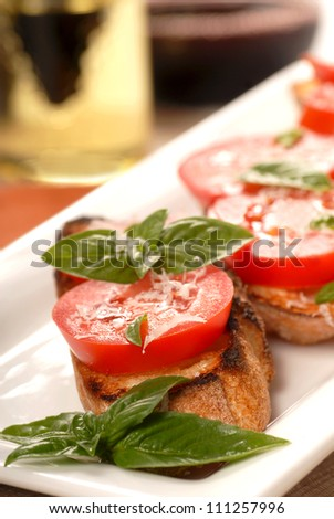 Delicious Bruschetta with tomato and basil on a white place with a glass of wine in the background along with an oil and vinegar vinaigrette.