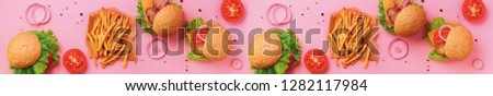 Delicious burger and french fries on a pink background. Multi-colored picture.