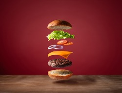 Delicious burger with floating ingredients on the wood table red background