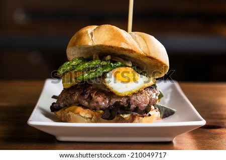 Delicious burger with onion, fried eggs, asparagus and french fries.