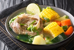 Delicious Caldo de res Mexican beef shank soup with vegetables close-up in a bowl on the table. horizontal