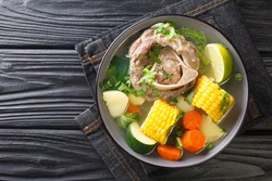 Delicious Caldo de res Mexican beef shank soup with vegetables close-up in a bowl on the table