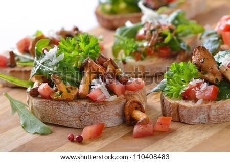 Delicious canapes with rucola-tomato-salad, fried chanterelles and parmesan cheese