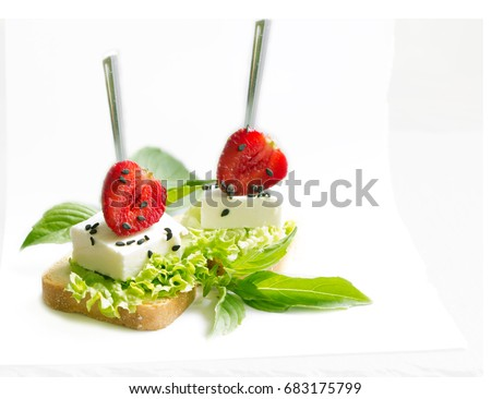 Shutterstock Delicious canapes wiyh feta cheese , strawberrys black sesame  and fresh basil leaves isolated on white