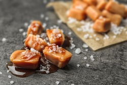 Delicious candies with caramel sauce and salt on gray background