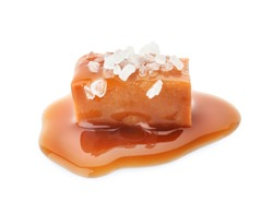Delicious candy with caramel sauce and salt on white background