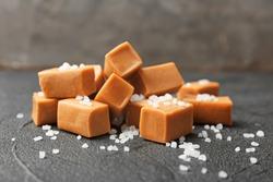 Delicious caramel candies with salt on dark background
