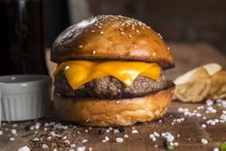 Delicious cheese burger on a rustic wooden table