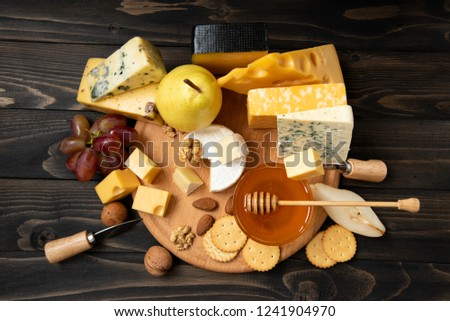 Delicious cheese on the table. Various types of cheese on a rustic wooden table. Assortment of cheeses with nuts, fruits and honey. top view