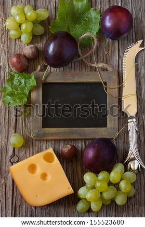 Delicious cheese with fruit and nuts and chalk blackboard for text on a wooden board.