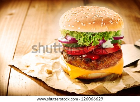 Delicious Cheeseburger Stacked High With A Juicy Beef Patty, Cheese, Fresh Lettuce, Onion And Tomato On A Fresh Bun With Sesame Seed Standing On Brown Paper On A Wooden Tabletop With Copyspace