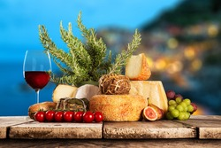 Delicious cheeses with red wine on wooden table.