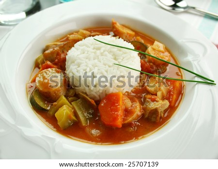 Delicious chicken gumbo with rice, sausage, peppers, onions, carrots and tomatoes. - stock photo