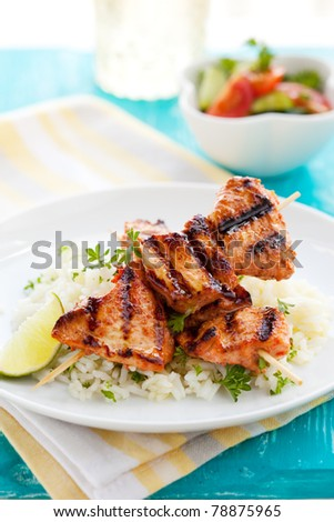 Delicious chicken masala skewers with rice and vegetable salad.