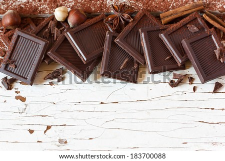 Delicious chocolate and spices on white wooden background.