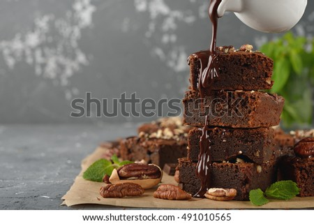 Stock Photo Delicious chocolate brownie with pecan nuts on a gray background