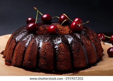 Delicious chocolate cake with glaze and cherries on the black background
