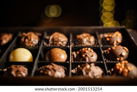 Delicious chocolate candies or truffle balls in box on table against light bokeh. Assorted Chocolate pralines.An assortment of fine chocolates in white, dark, and milk chocolate with nuts.