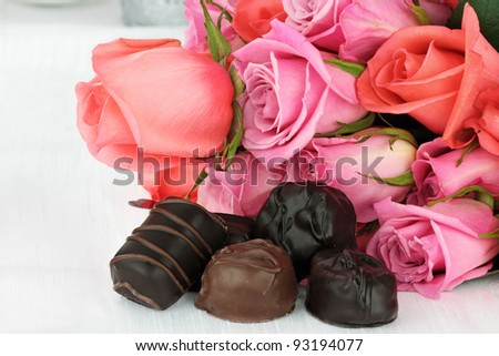 Delicious chocolate candies with a bouquet of roses.