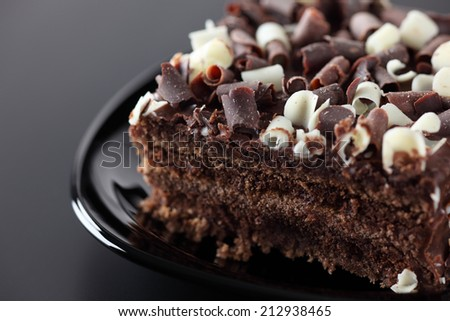 Delicious chocolate dessert is on black plate. Black background.