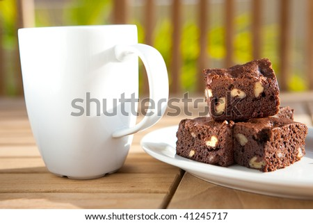 Delicious chocolate fudge brownie with pecan and walnut served with coffee