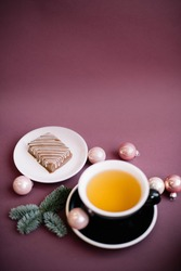 Delicious chocolate on the saucer and a cup of green tea, decorated with pink baubles and spruce branches on the burgundy coloured background, vertical photo