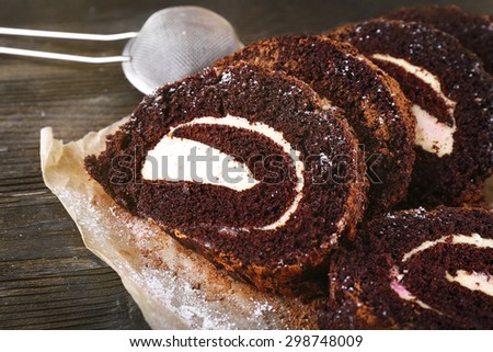 Delicious chocolate roll on parchment, closeup