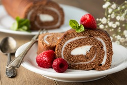 Delicious chocolate roll sponge cake with vanilla cream and mint leaves, Desert sweet food