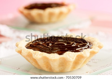Delicious chocolate tarts with chocolate frosting and pink background.
