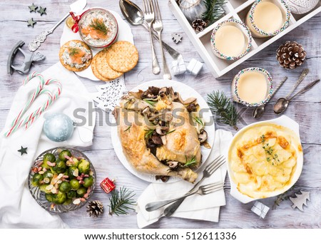 Delicious Christmas themed dinner table with roasted chicken, appetizers and desserts. Top view. Holiday concept.
