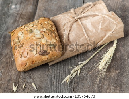 Delicious ciabatta packed in paper on a wood table