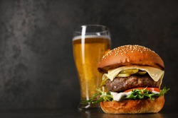 Delicious classic burger with cutlet and glass of cold beer on a stone background. Harmful and fast food.