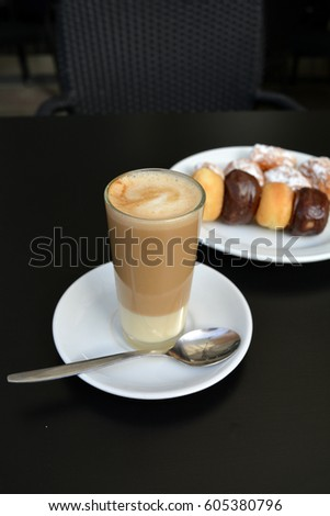Delicious coffee on a glass cup on a black background.  #605380796