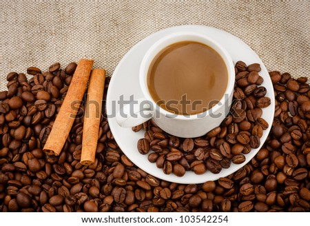 Delicious Coffee with Milk in a White Ceramic Cup on a Saucer, Roasted Coffee Beans, Cinnamon on a Sacking background