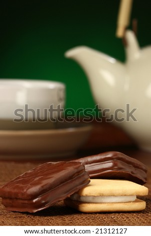 Delicious cokies, some tea behind, chocolate series