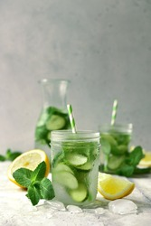 Delicious cold summer lemonade with cucumber and mint in a mason jars on a light  slate, stone or concrete background.