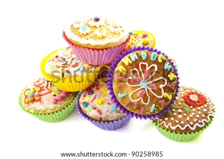 Delicious colorful cupcakes on a pile over white
