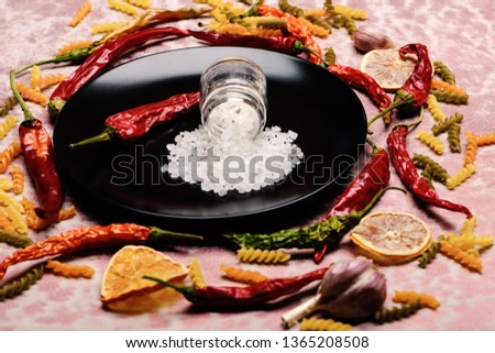 delicious colorful Italian pasta, spice in jar and chili pepper on ceramic plate, orange, garlic on pink textured background, side view #1365208508