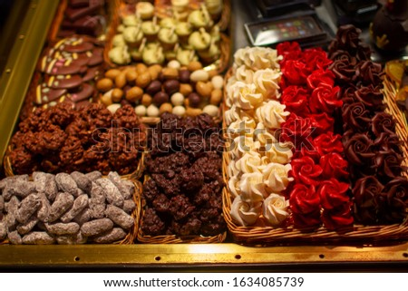 Delicious confectionery variety in baskets, on a food market stall: chocolate roses, glazed nuts and dried fruits, candies, sweets close up photo