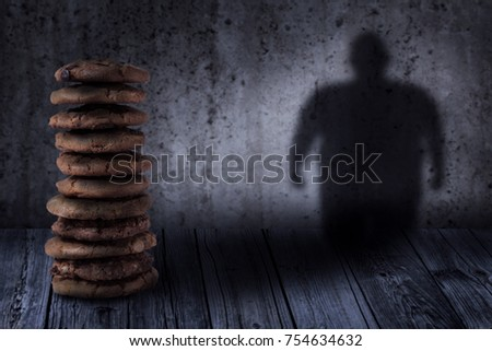 delicious cookies on table and fat person shadow on vintage backgrounds, overweight and diet, health care concepts