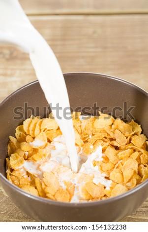 Delicious corn flakes with milk on white background