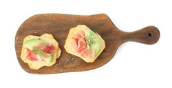 Delicious crackers with avocado, prosciutto and dill on white background, top view
