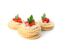 Delicious crackers with humus, bell pepper and parsley on white background