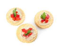 Delicious crackers with humus, bell pepper and parsley on white background, top view