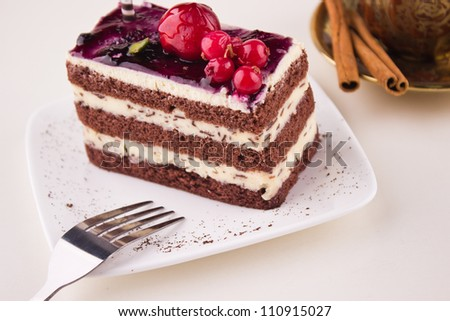 Delicious cream chocolate cake with cherry berry and coffee cup with cinnamon