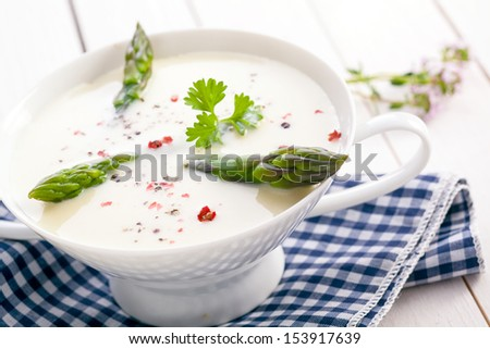 Delicious cream of asparagus soup with green asparagus shoots served in a dainty white bowl on a checkered cloth