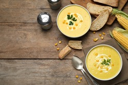Delicious creamy corn soup served on wooden table, flat lay. Space for text